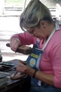 Janete prepara uma plaquinha com seu formão e batedor