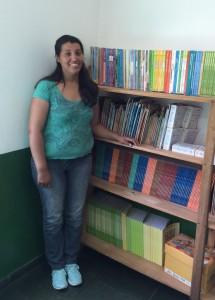 A professora Tatiana e a estante com livros para alunos do 1º ao 3º ano