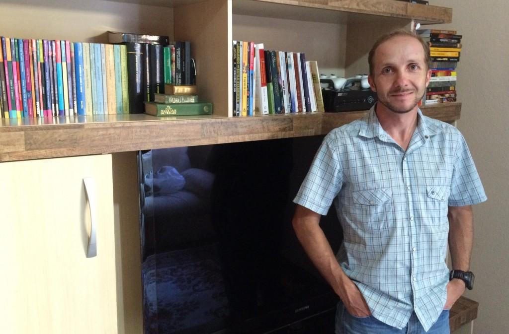 Ivan Pires diante de alguns de seus livros